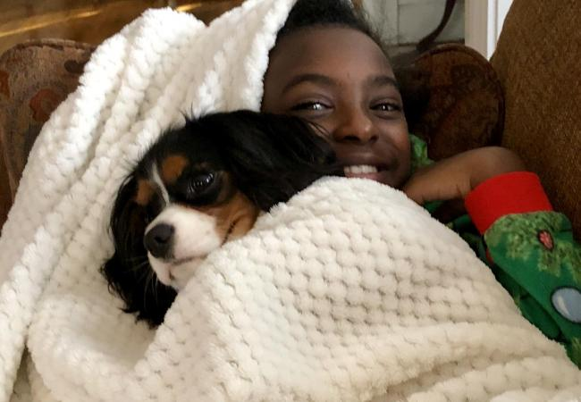 Young girl laying with a King Charles Spaniel